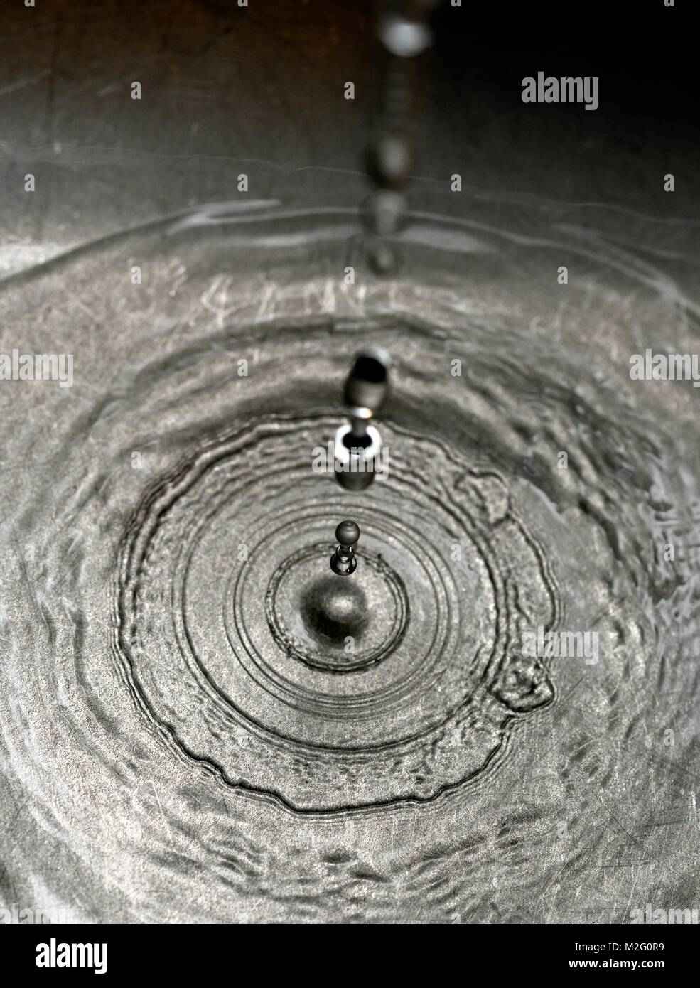 water droplets dropping into a stainless steel sink - Stock Image