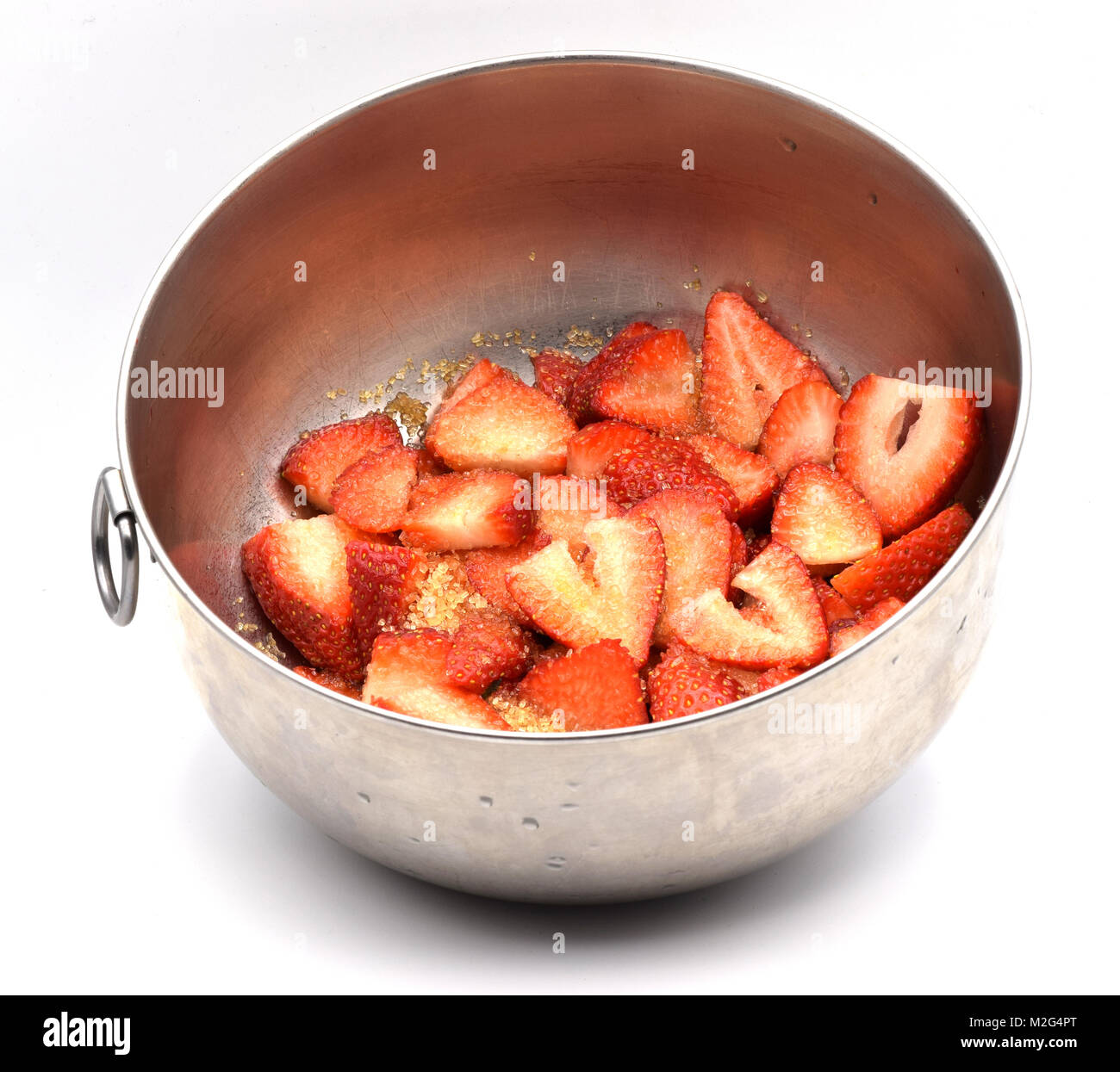 Cut strawberries covered with sugar in a metal bowl on a seamless white background. - Stock Image