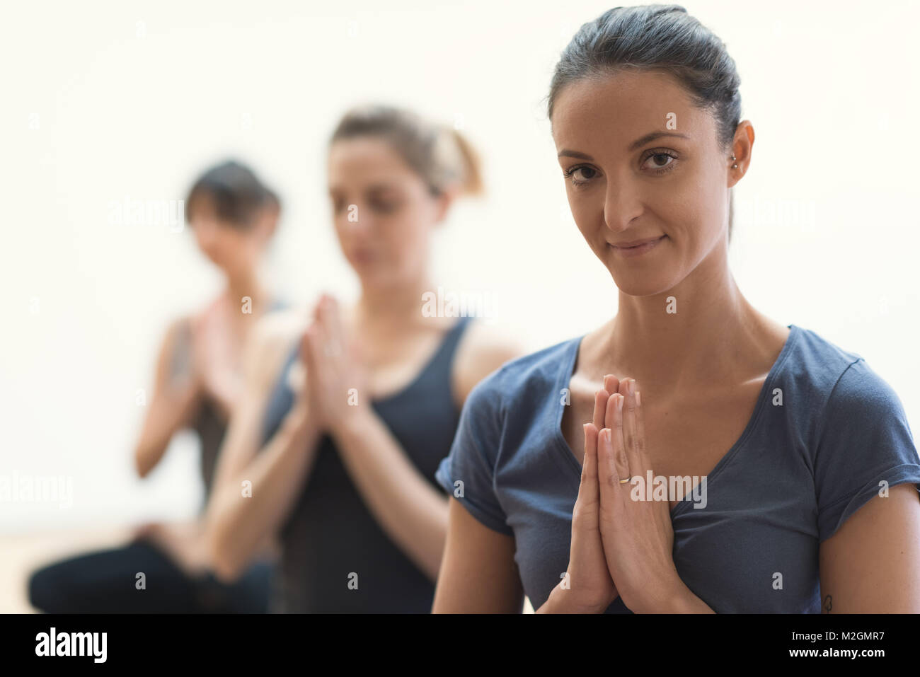 Women practicing yoga and mindfulness meditation together, they are clasping hands and relaxing, healthy lifestyle - Stock Image