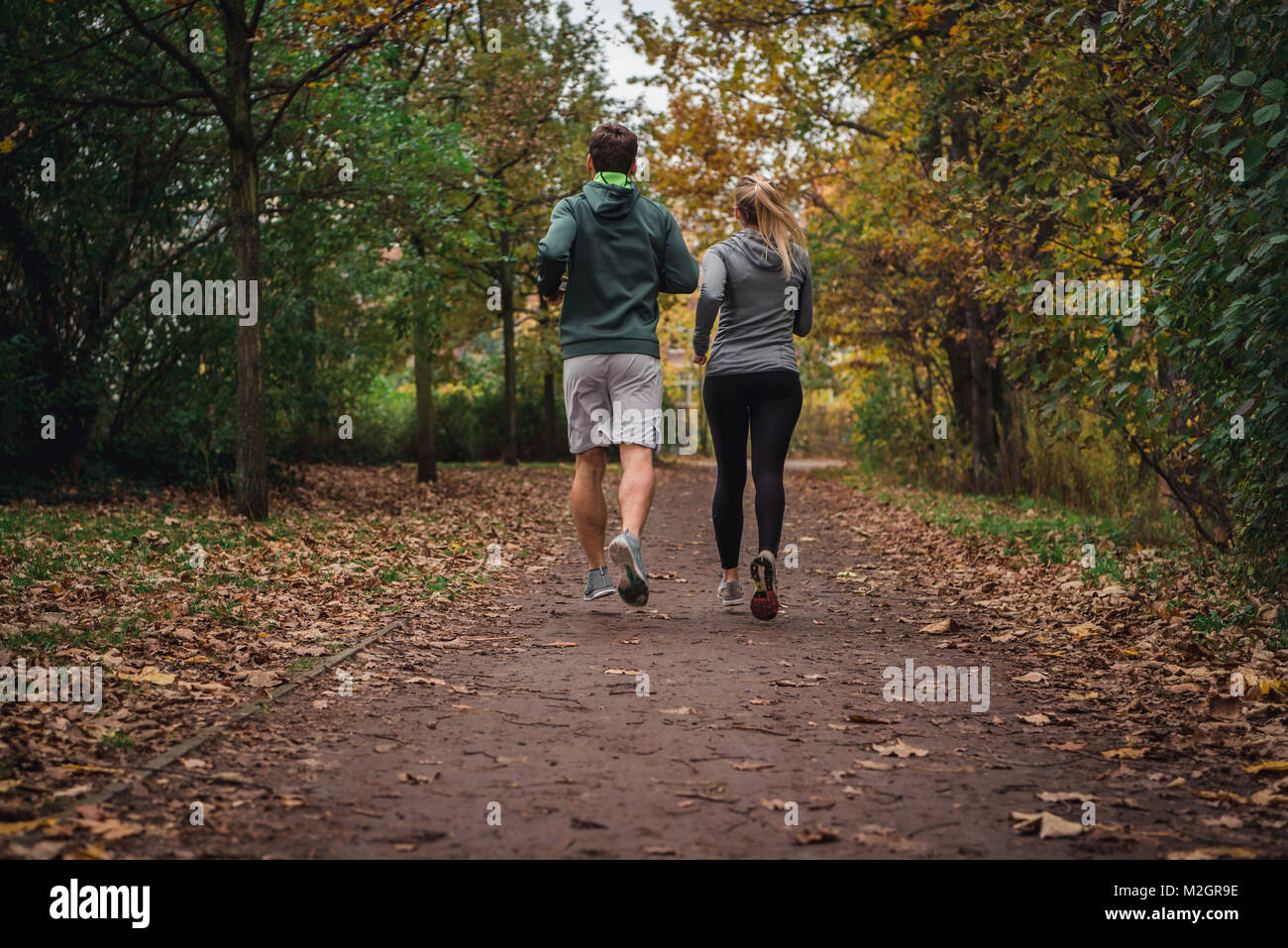 Caucasian man and woman running through the park in the Autumn Fall season down an empty trail. - Stock Image