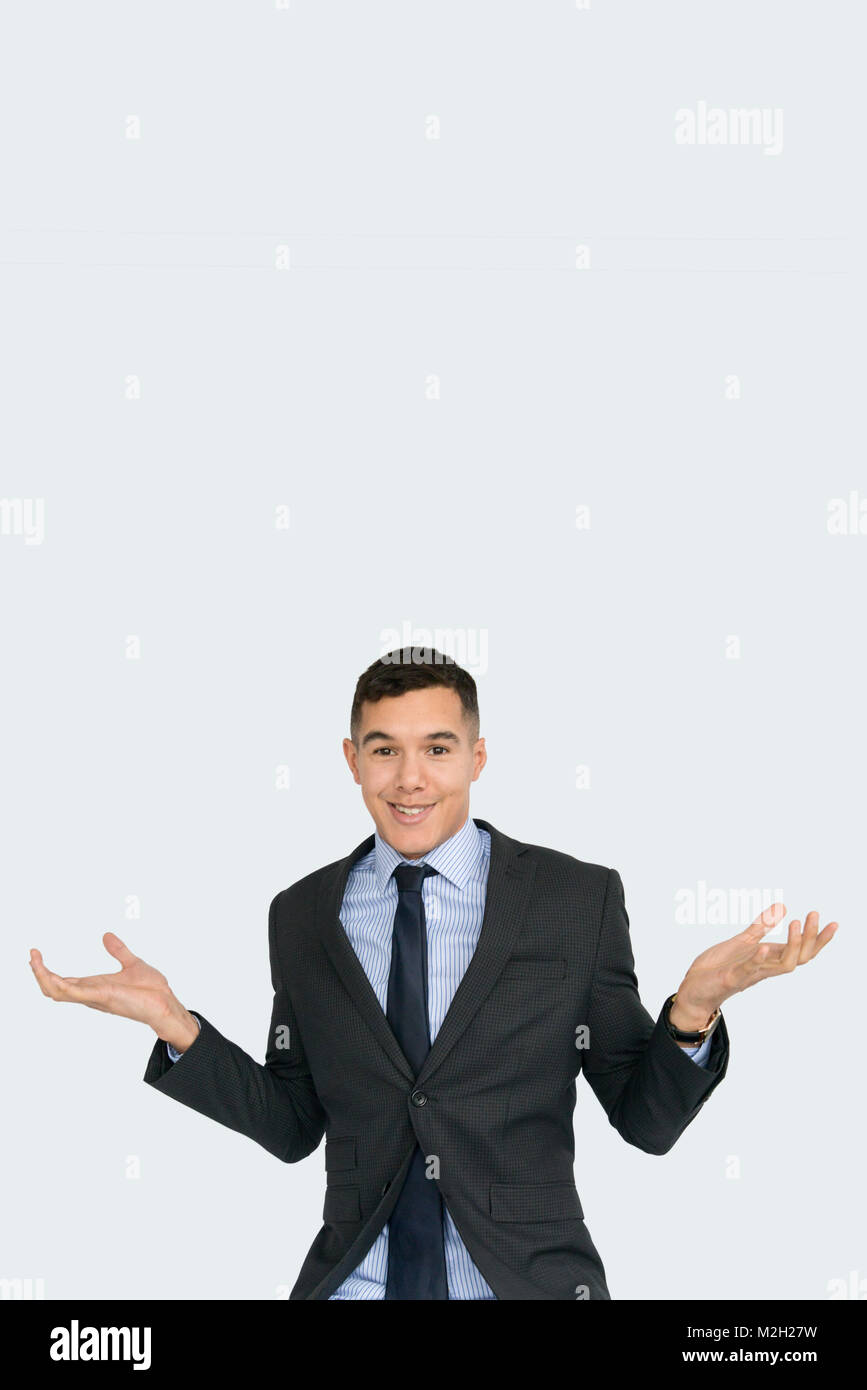 portrait of a handsome, young, well dressed man in a suit and tie shrugs his shoulders and opens his arms 'its - Stock Image