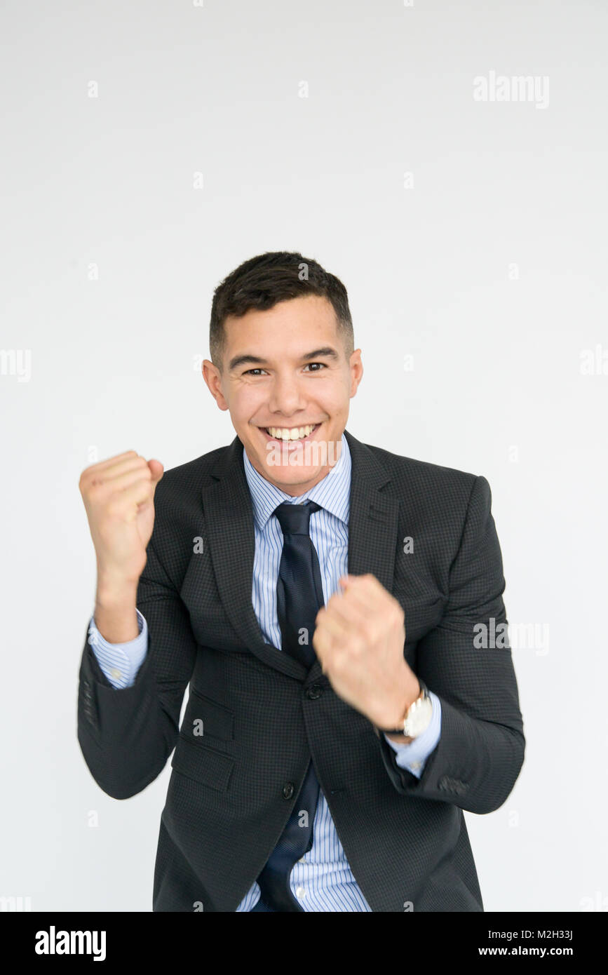 Portrait of an excited, smiling, handsome, well dressed young man who is punching the air - Stock Image
