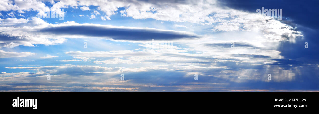 blue sky with clouds panorama. panoramic view, sun shines through clouds. cloudscape scenery - Stock Image