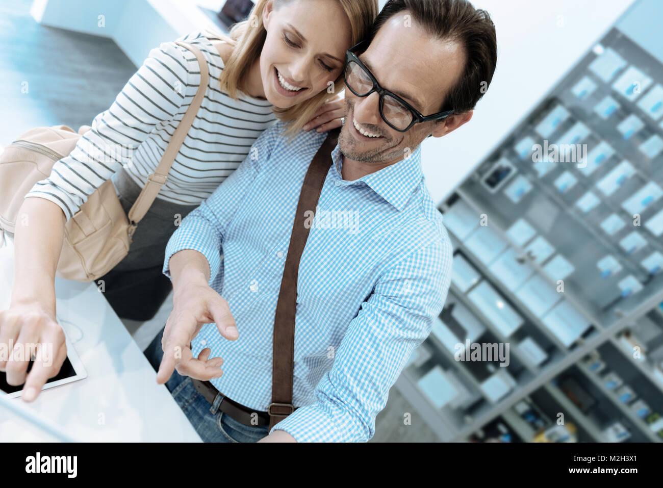 Loving couple choosing telephone together - Stock Image