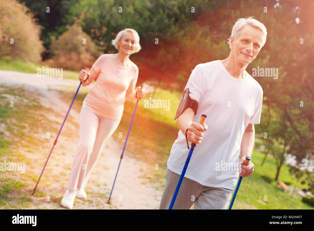 Optimistic elderly family walking with crutches in fresh air - Stock Image
