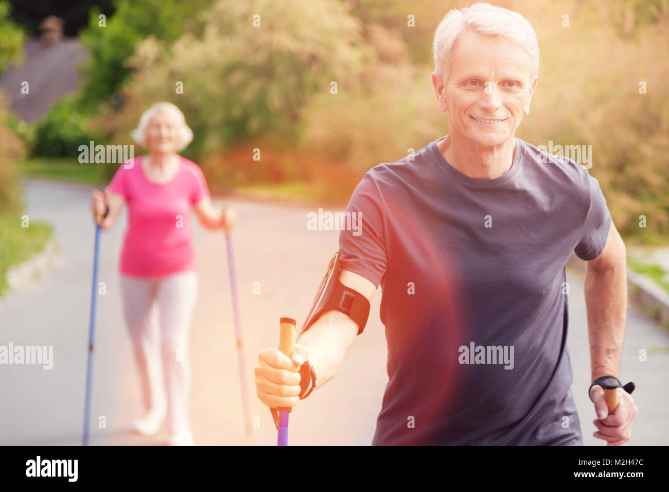 Waist up of enthusiastic elderly man with walking cane - Stock Image