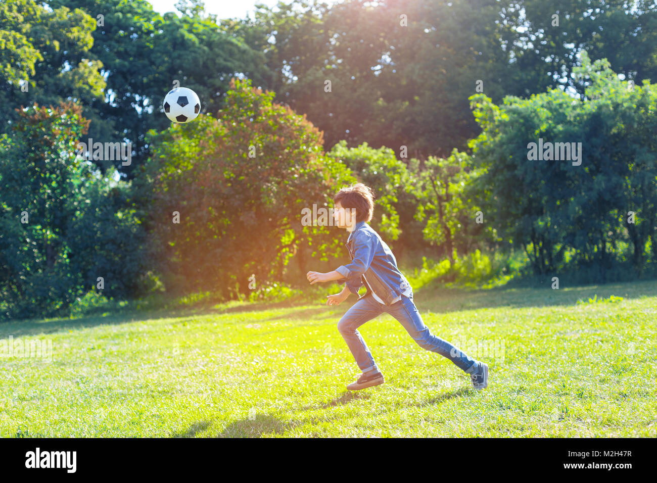 Active teen boy playing football outdoors - Stock Image