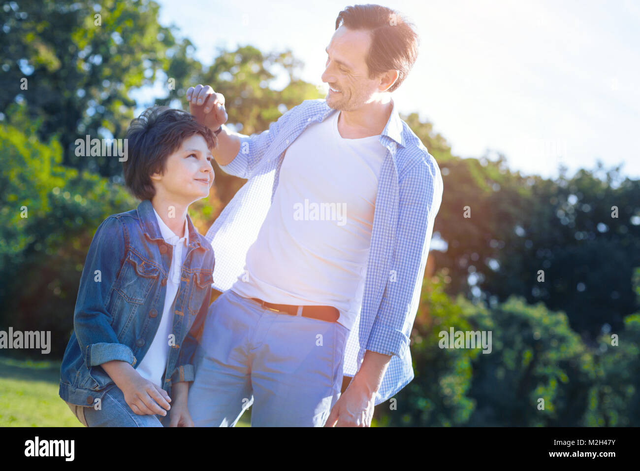 Cheerful father and son smiling to each other - Stock Image