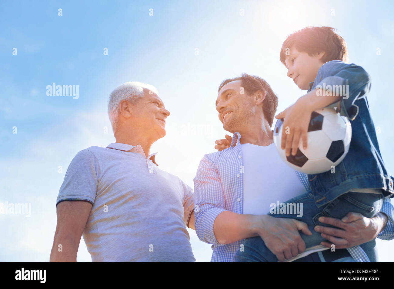 Three generations of men spending time outdoors - Stock Image