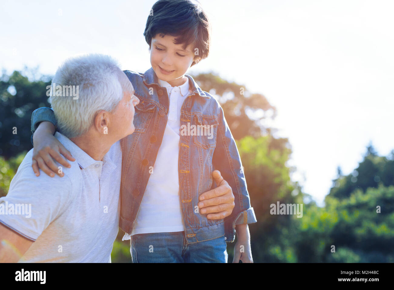 Cute preteen boy talking to loving grandfather outdoors - Stock Image