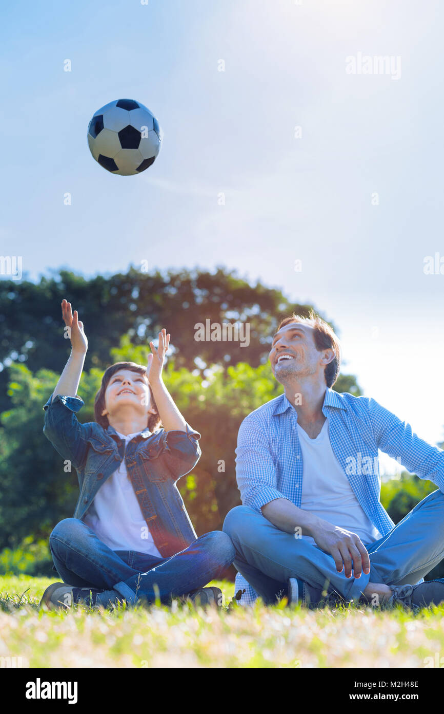 Family football fans playing outdoors together - Stock Image