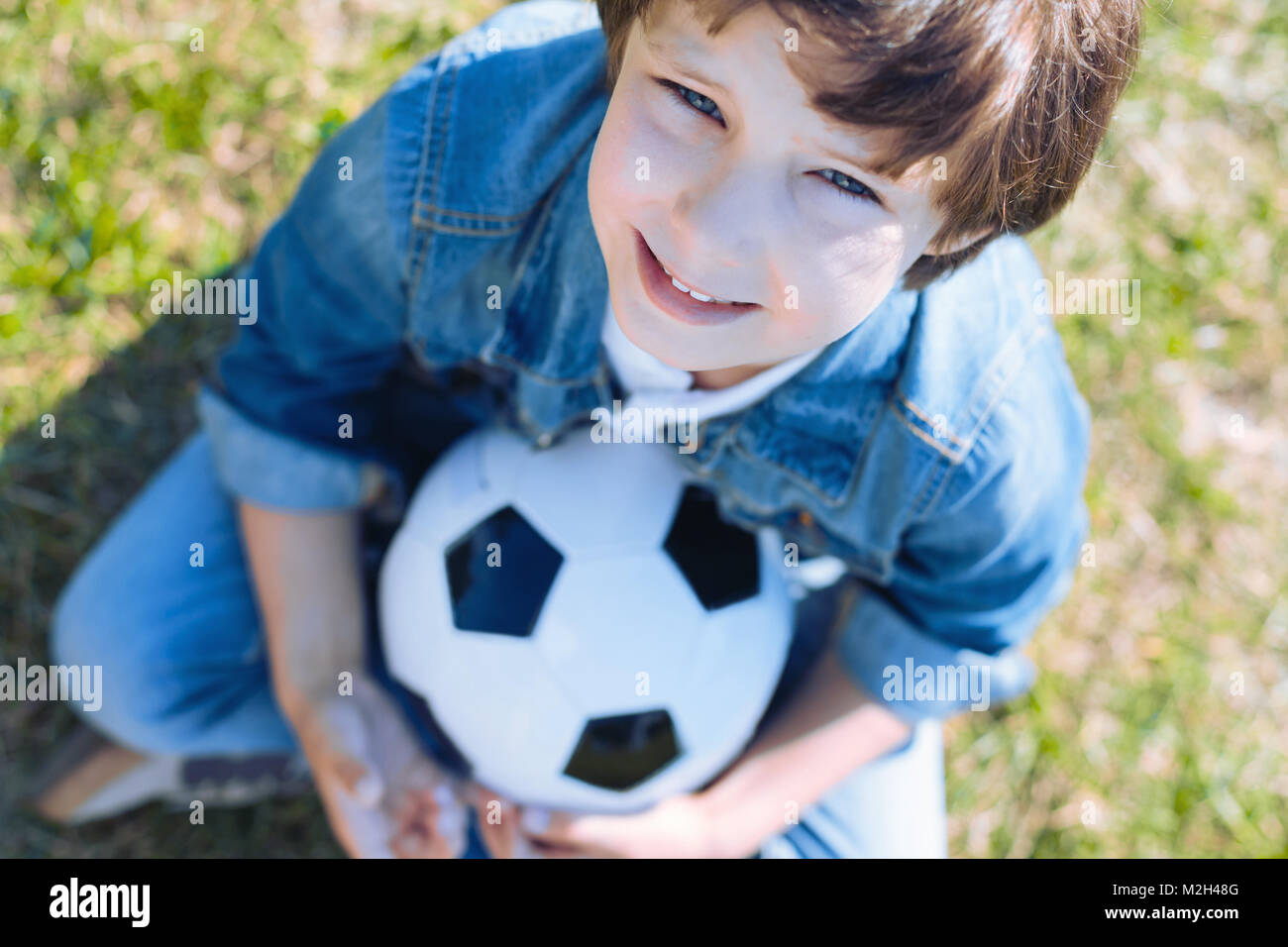 Cute boy with ball smiling after playing soccer - Stock Image