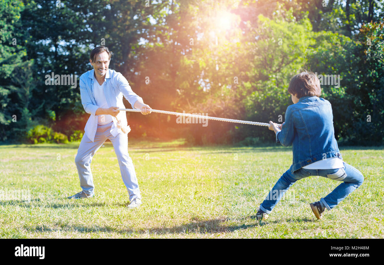 Excited father and son playing tug of war together - Stock Image