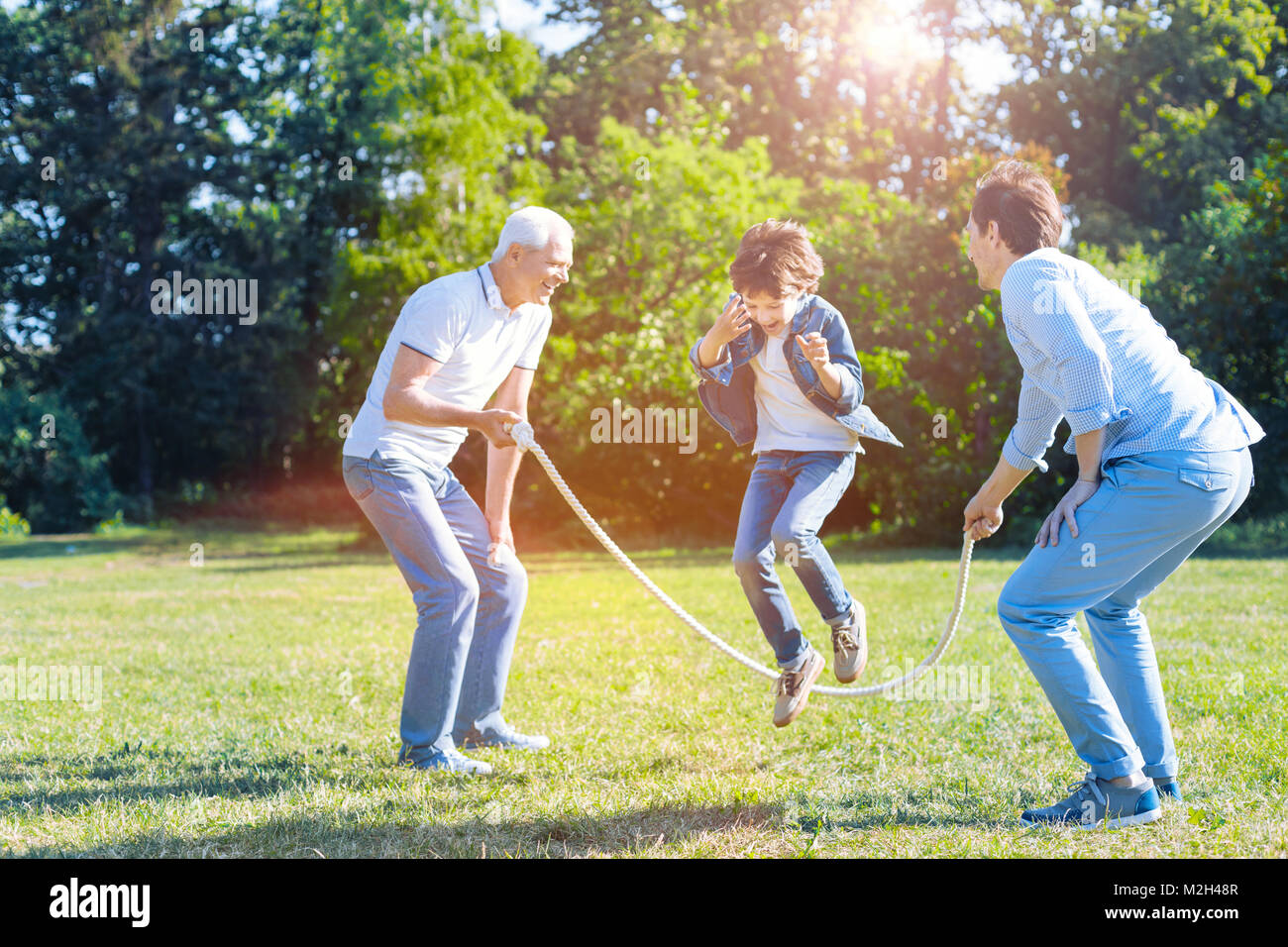 Supportive family playing with jump rope in park - Stock Image