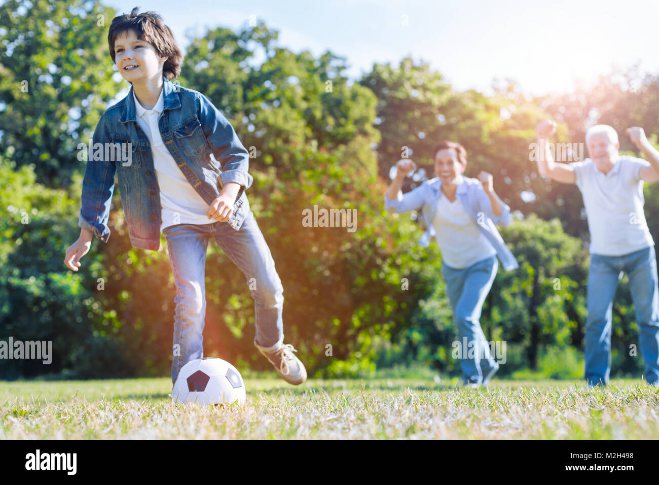 Father and granddad cheering for grandson playing football - Stock Image