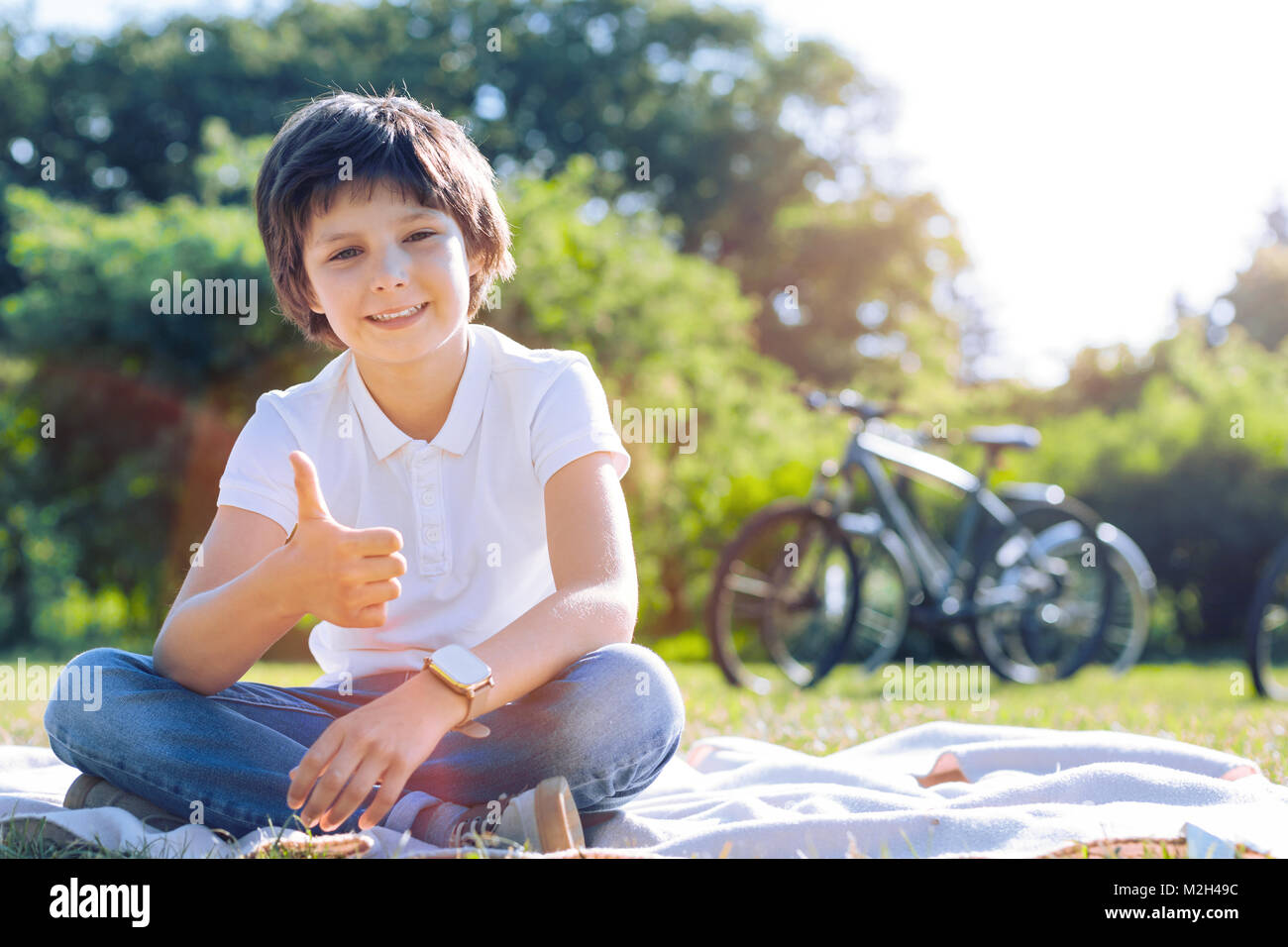 Smiling preteen boy thumbing up outdoors - Stock Image