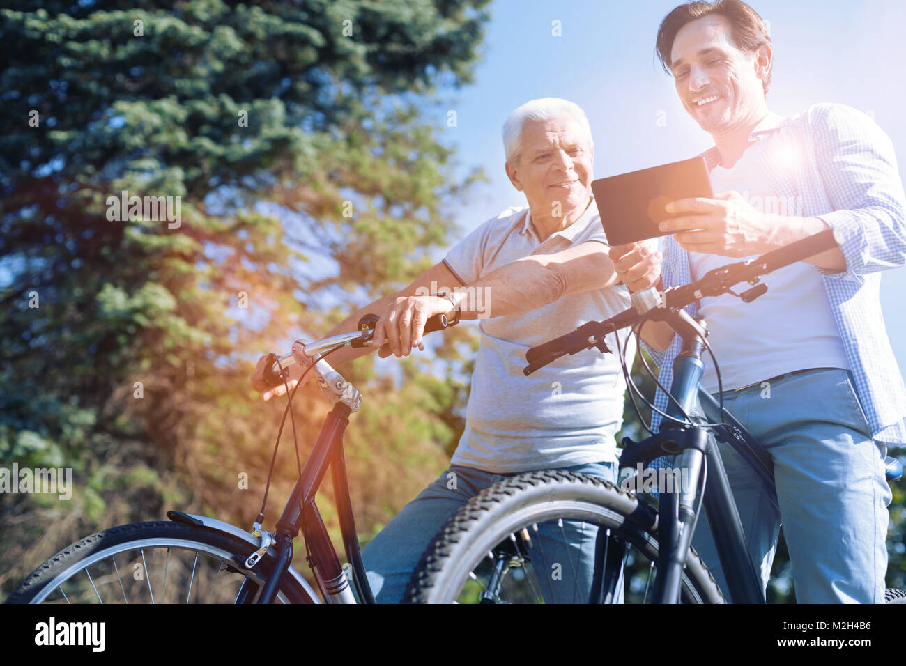 Senior dad and son smiling while looking at tablet computer - Stock Image