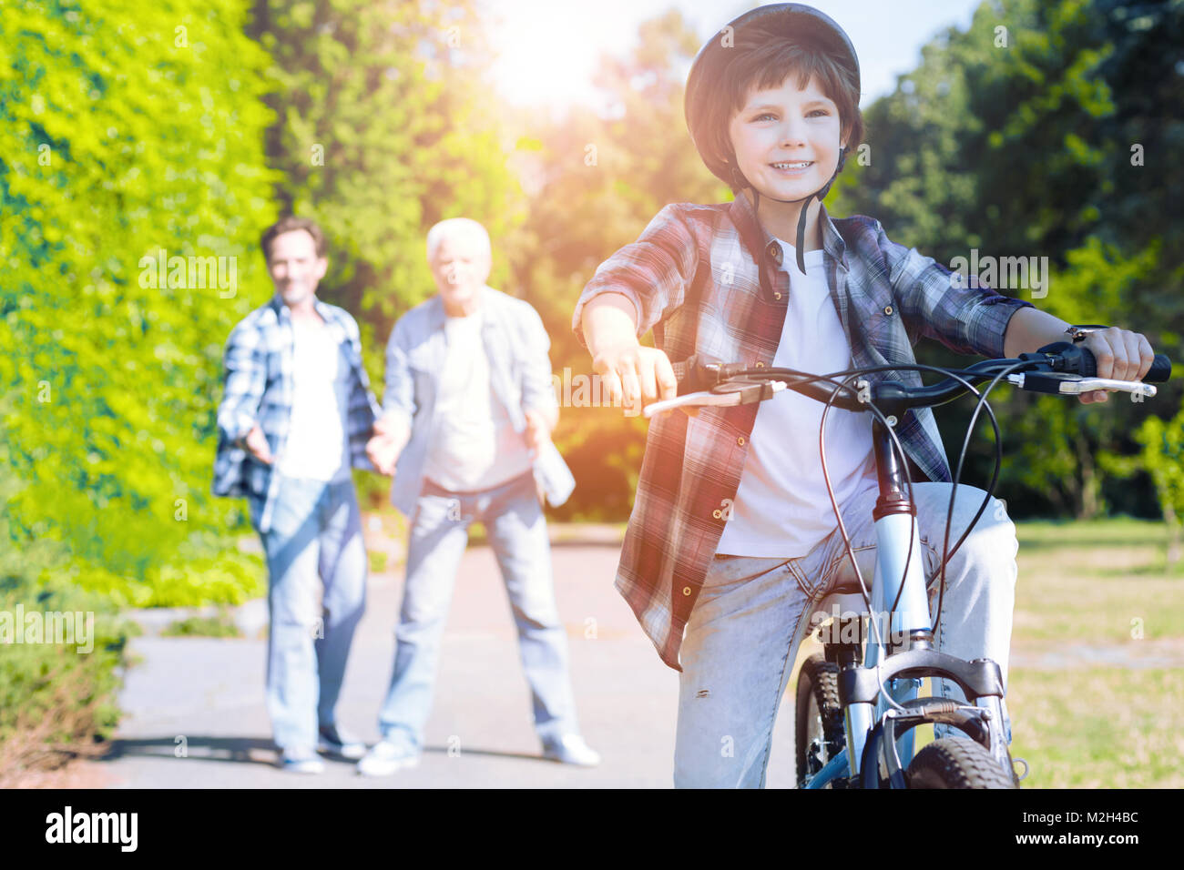 Excited kid learning to ride bicycle outdoors - Stock Image