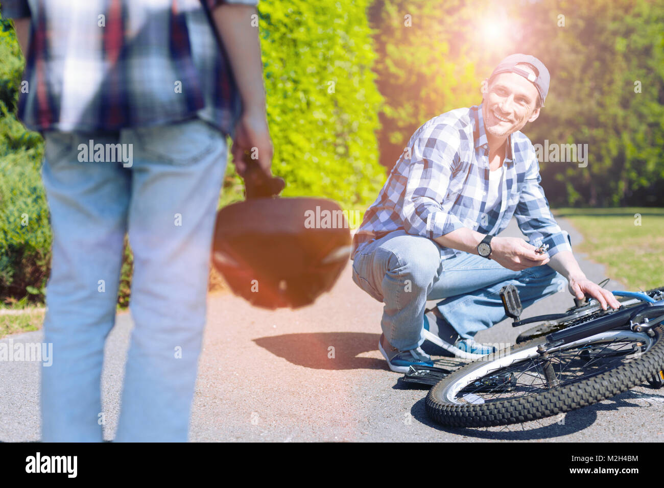 Son watching father fixing bicycle in park - Stock Image