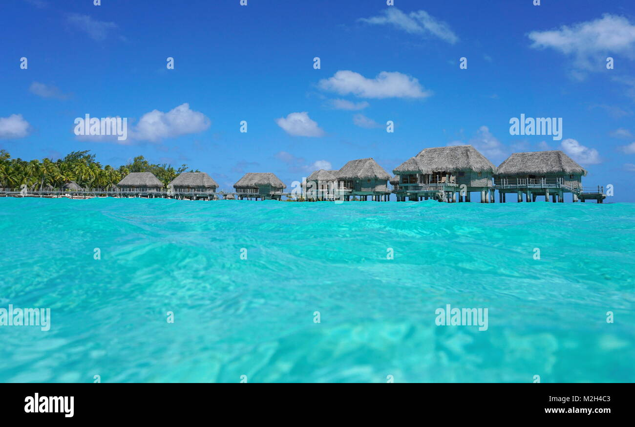 Over water bungalows with thatched roof in a tropical lagoon, seen from sea surface, Tikehau atoll, Tuamotus, French Stock Photo