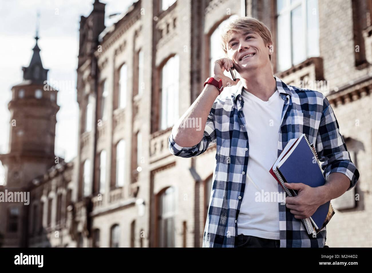 Joyful positive student sharing news - Stock Image