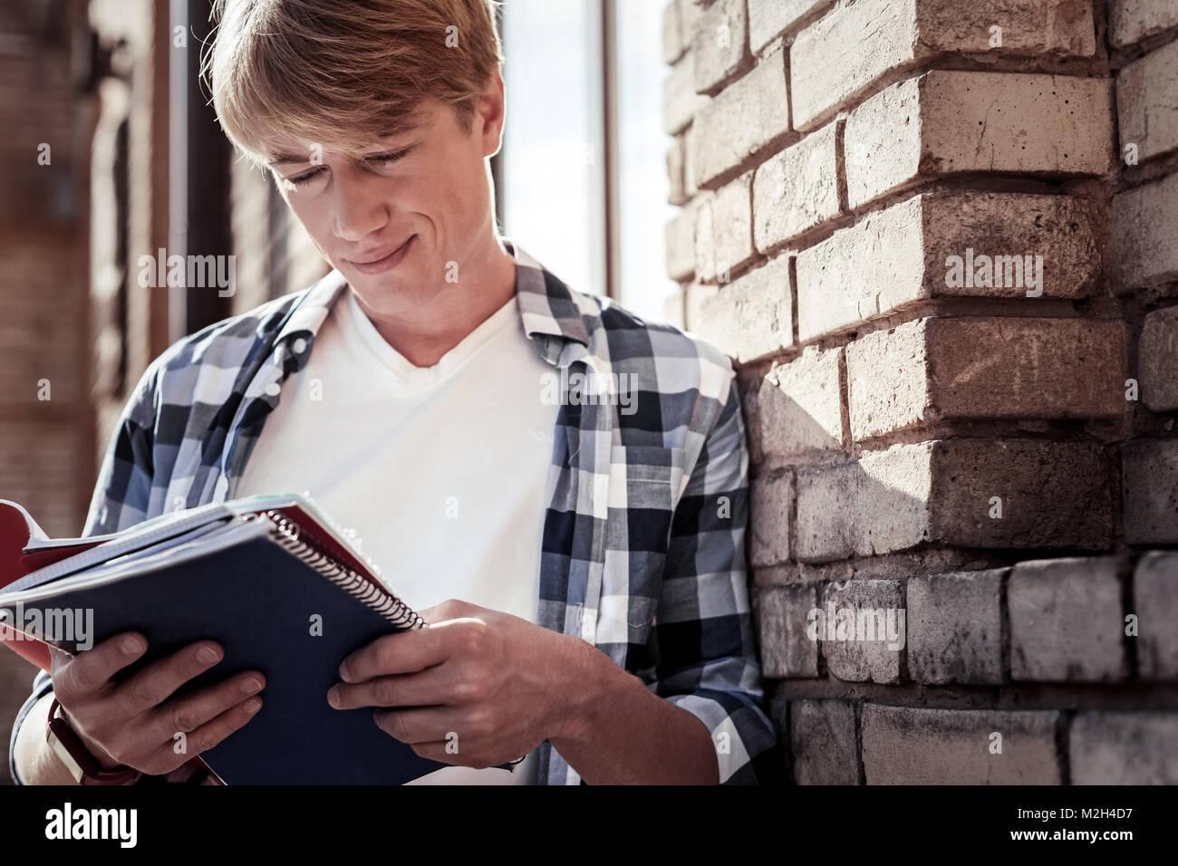 Positive joyful student reading his notes - Stock Image