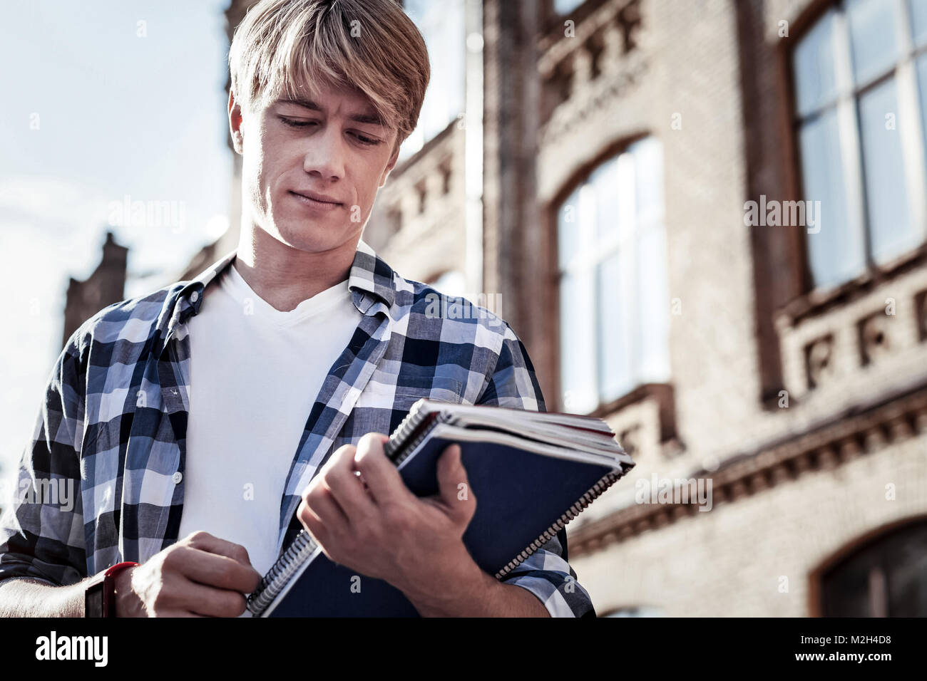 Nice serious man looking at his books - Stock Image