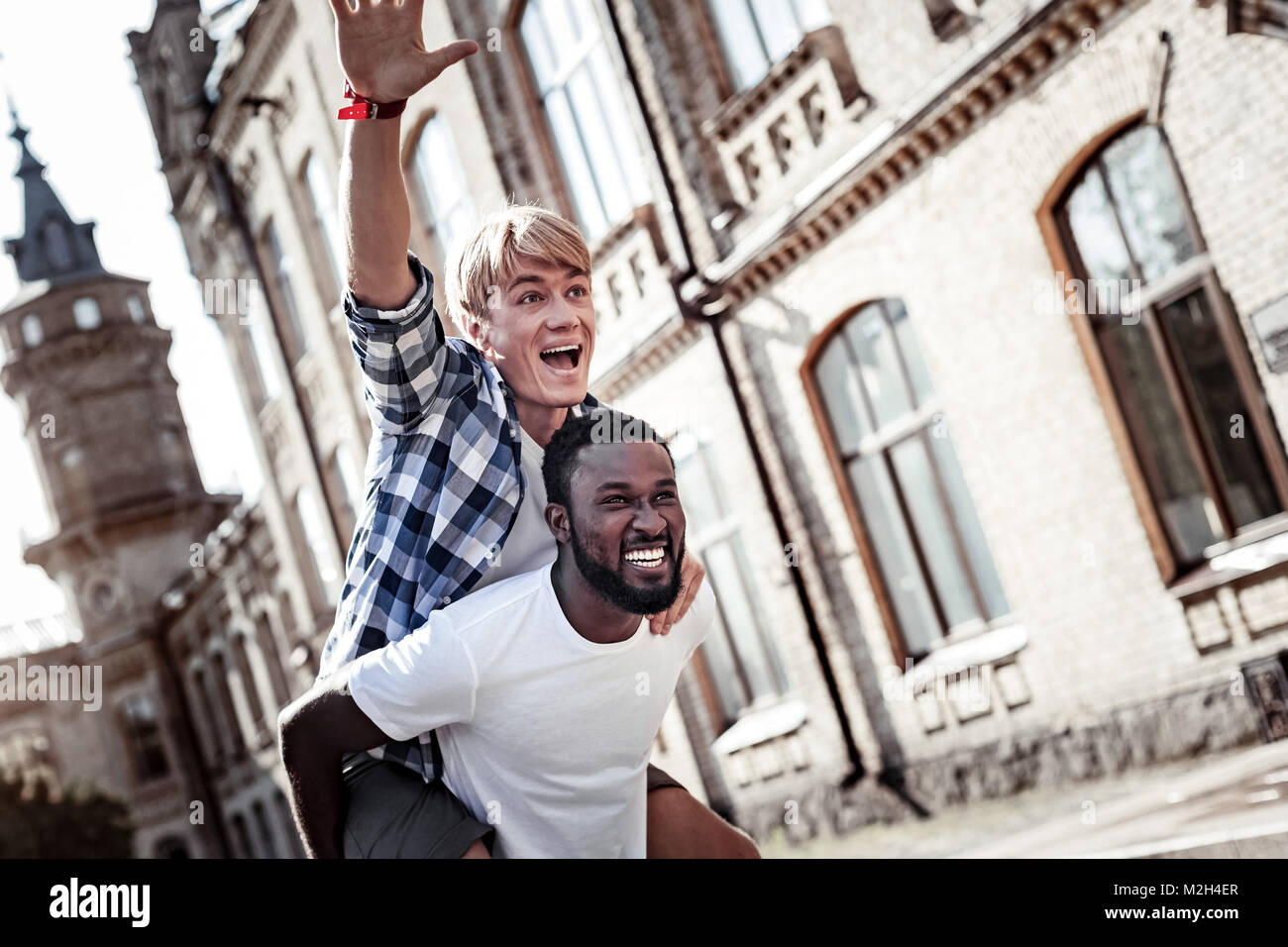 Delighted strong man carrying his friend - Stock Image