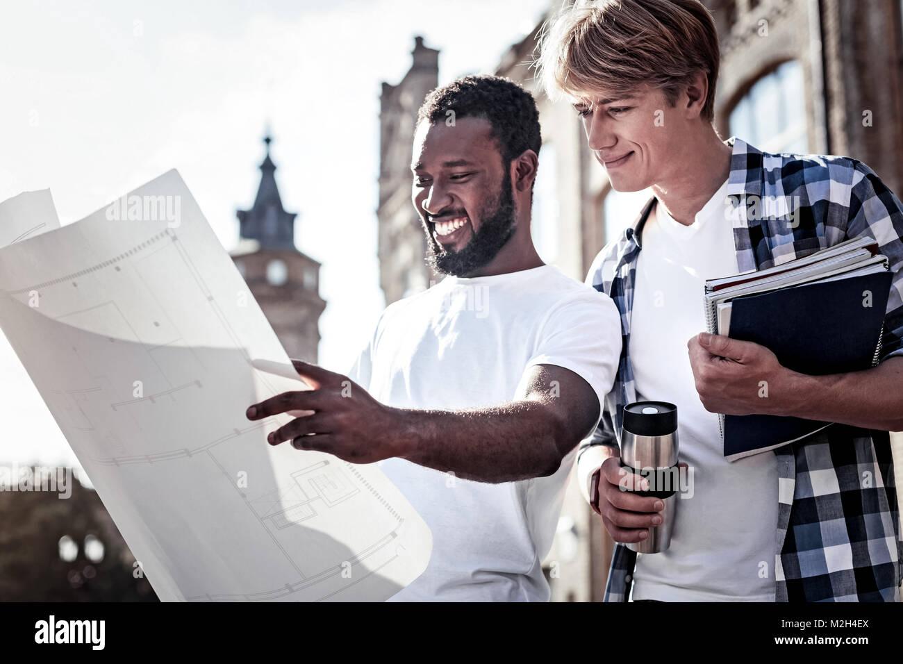 Joyful positive student looking at the blueprint - Stock Image