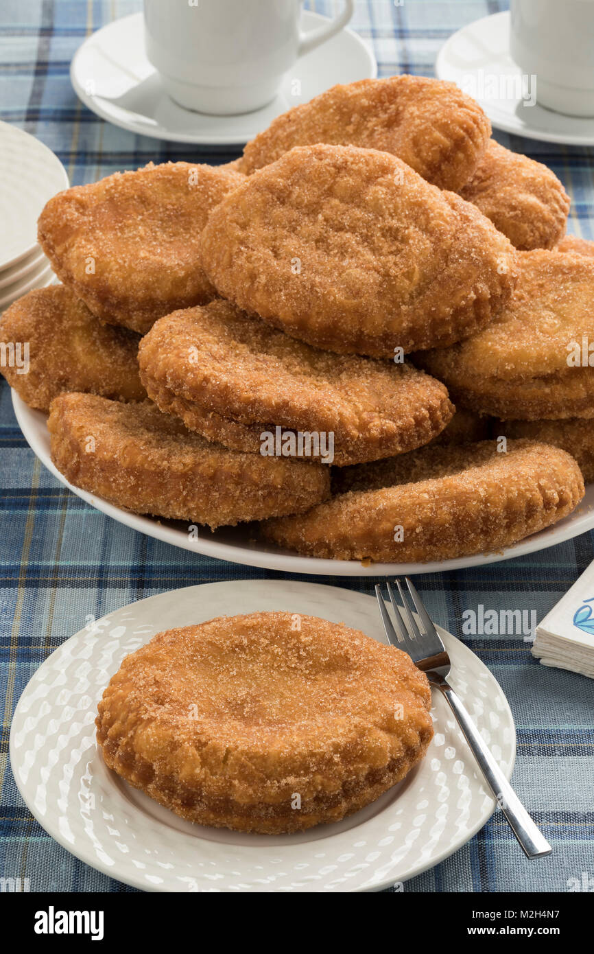 Dish with  sugared fried apple fritters or appelflappen, a traditional Dutch pastry for New Year's Eve - Stock Image