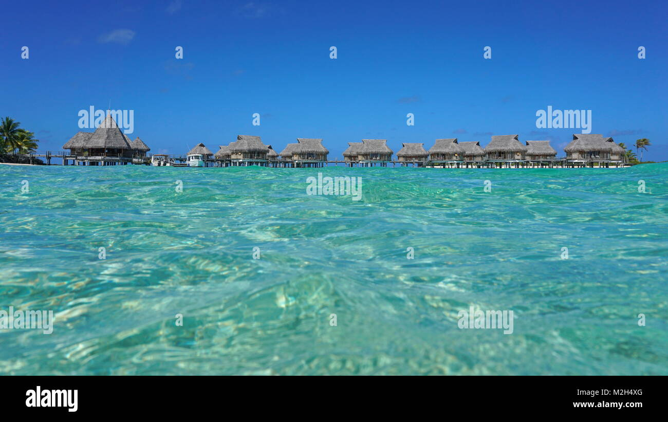 Tropical resort with thatched bungalows in the lagoon seen from sea surface, Tikehau atoll, Tuamotus, French Polynesia, - Stock Image