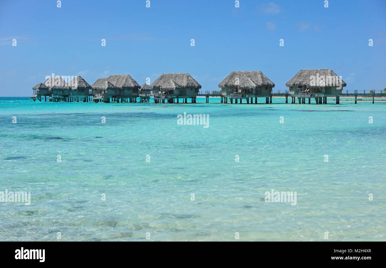 Tropical bungalows overwater in a lagoon with turquoise water, Tikehau atoll, Tuamotus, French Polynesia, Pacific - Stock Image