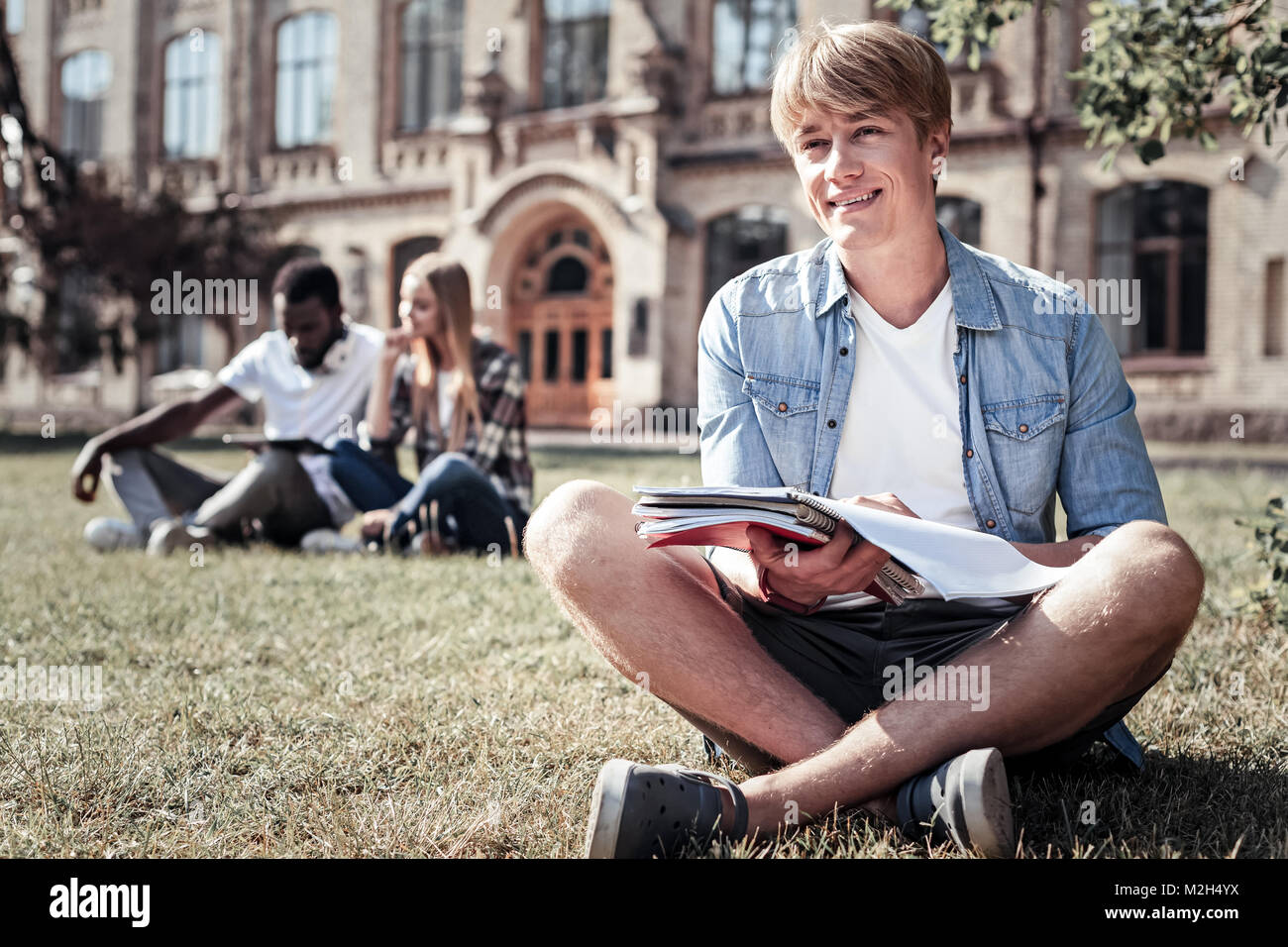Nice positive student sitting on the grass Stock Photo