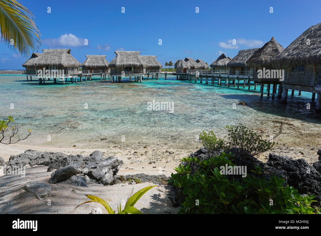 Tropical island resort with bungalows on stilt in the lagoon, Tikehau atoll, Tuamotus, French Polynesia, Pacific - Stock Image