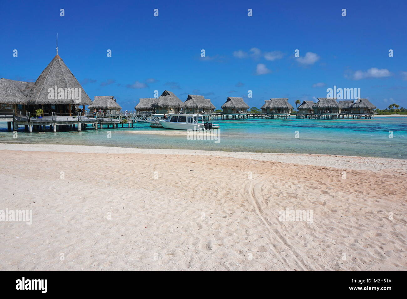 Tropical resort, beach sand with thatched bungalows over water in the lagoon, Tikehau atoll, Tuamotus, French Polynesia, - Stock Image