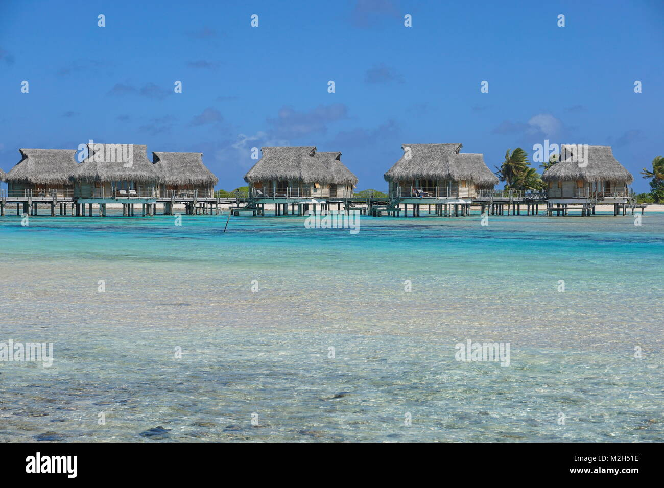 Tropical resort with overwater bungalows in the lagoon, Tikehau atoll, Tuamotus, French Polynesia, Pacific ocean, - Stock Image