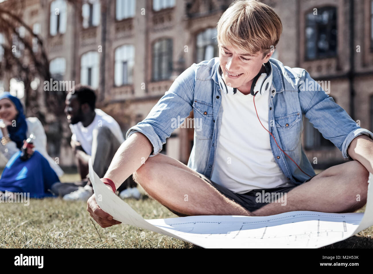 Happy cheerful student holding a blueprint - Stock Image