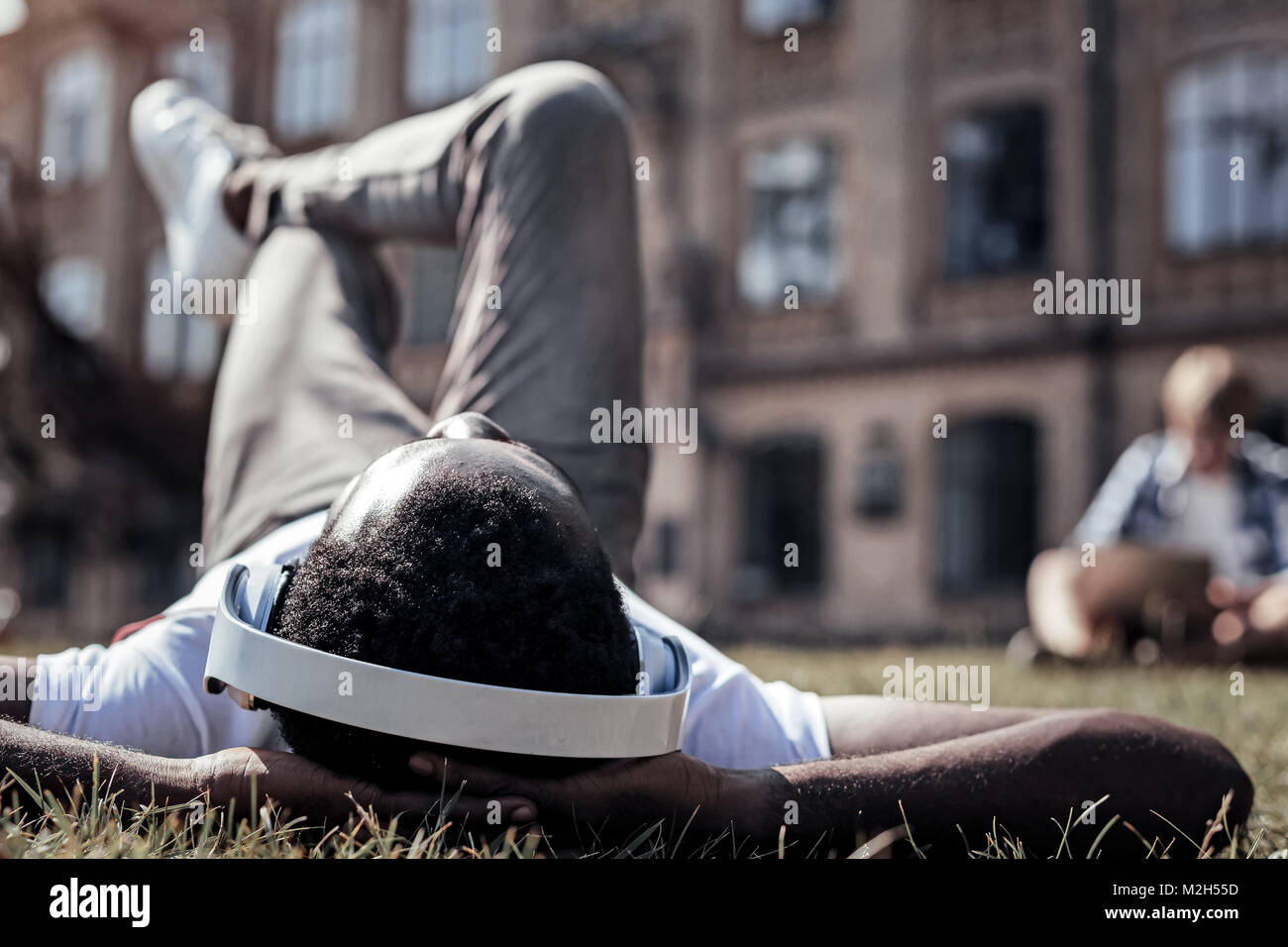 Happy delighted man relaxing in the park - Stock Image