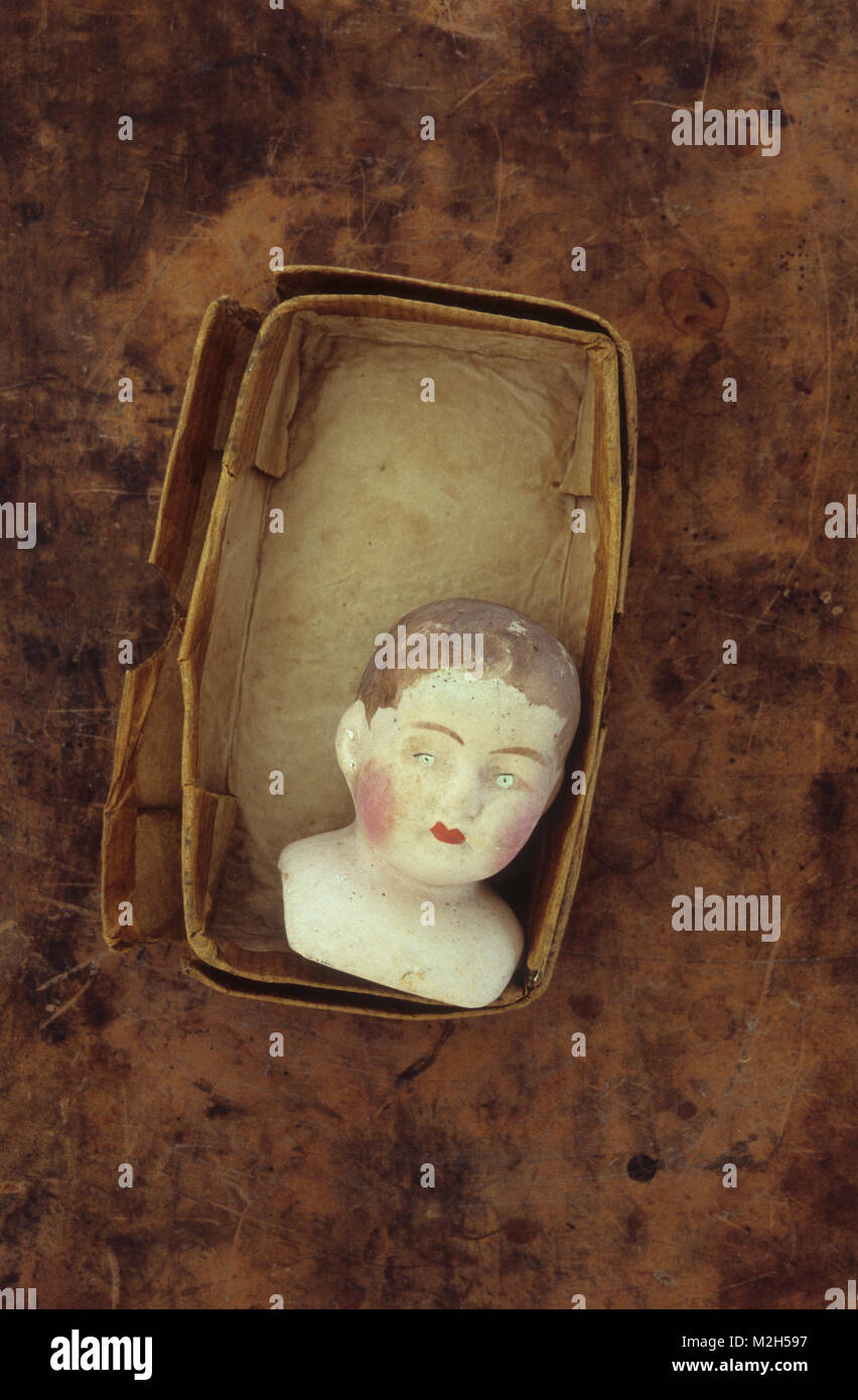Vintage bisque dollhead of boy with red cheeks and sad expression lying in old box - Stock Image