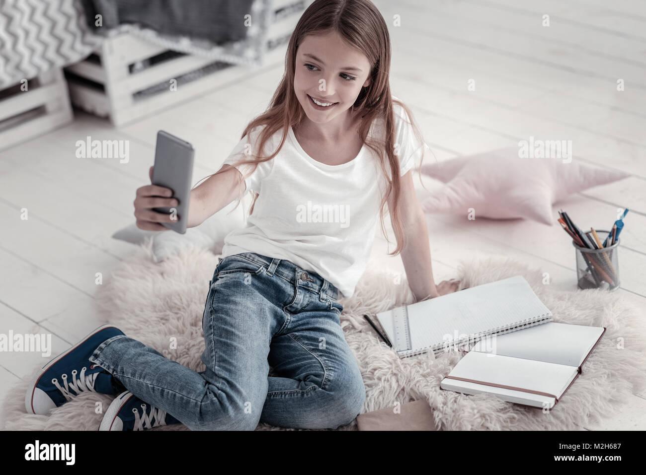 Smiling girl taking selfies on the floor - Stock Image