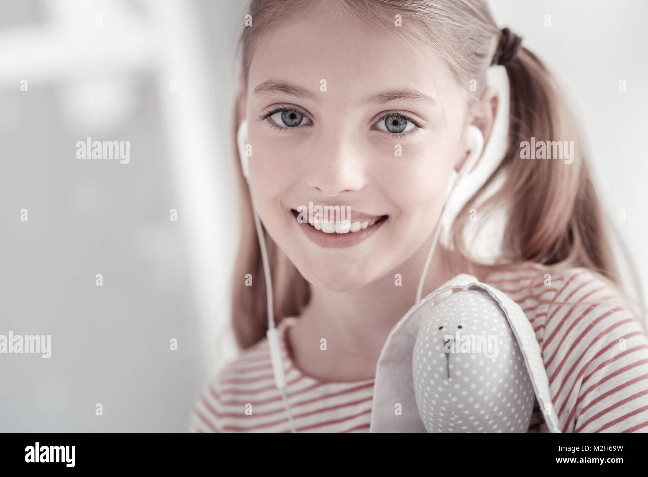 Inspired girl with headset and her toy - Stock Image