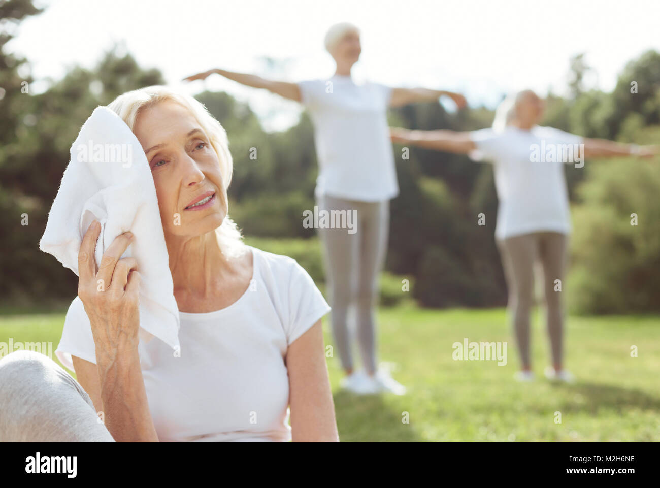 Pleasant tired woman holding a towel - Stock Image