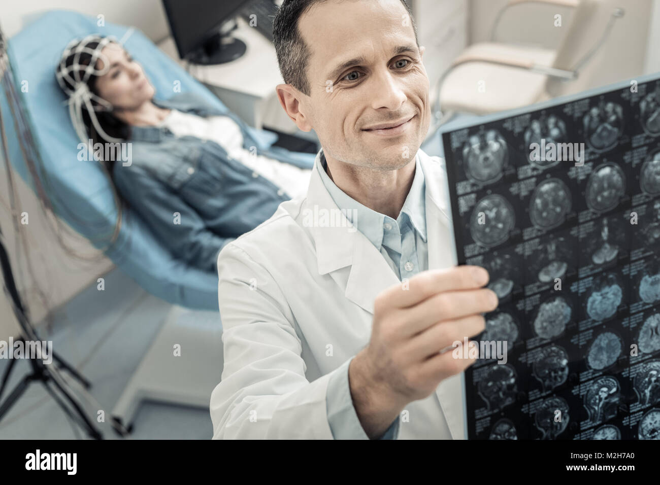 Positive delighted doctor looking at the X ray photo - Stock Image