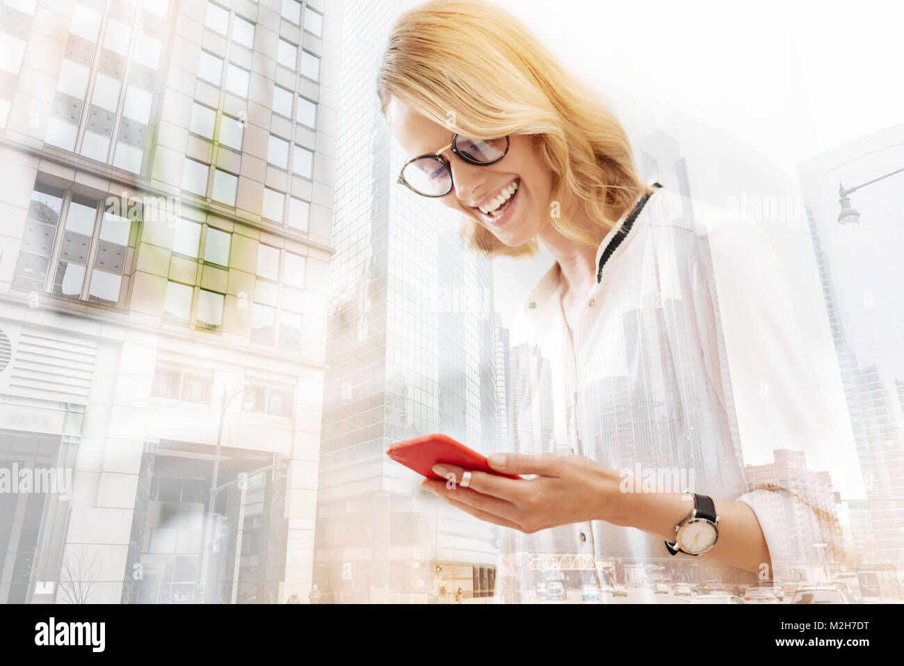 Attentive young woman looking at the mobile phone - Stock Image