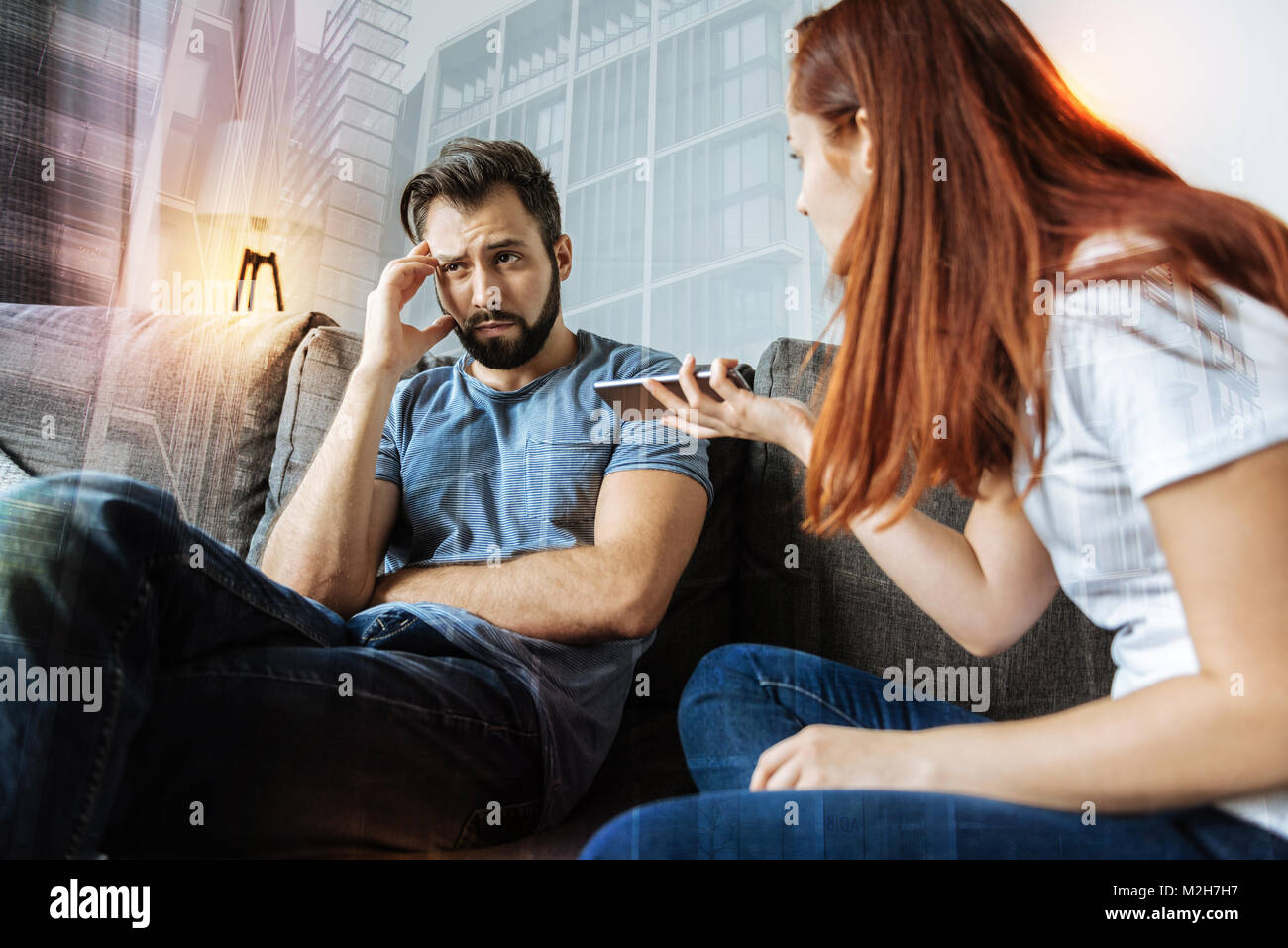 Jealous woman showing a phone to her boyfriend while having suspicions - Stock Image
