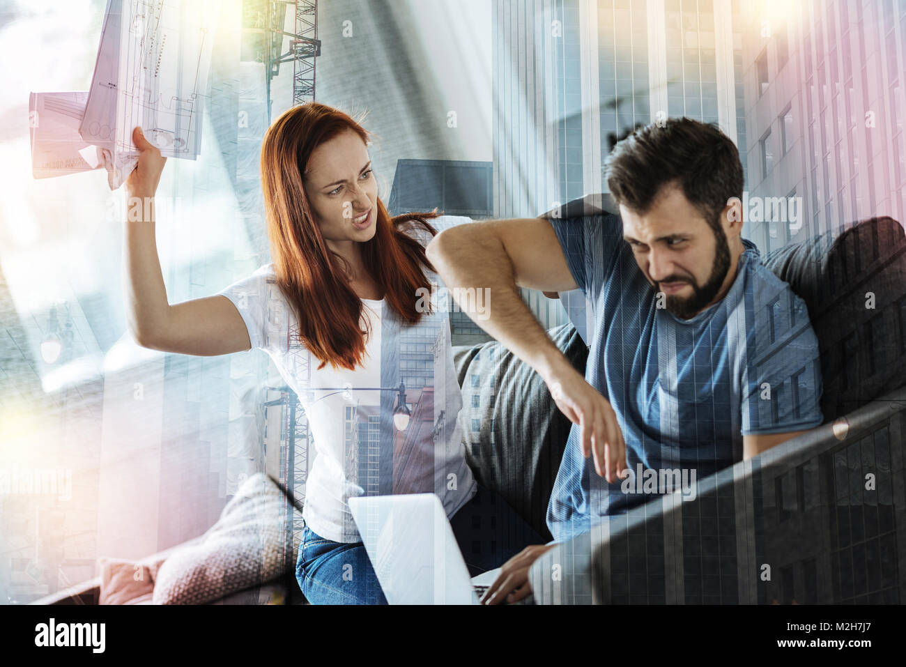 Furious young woman throwing documents into her boyfriend - Stock Image