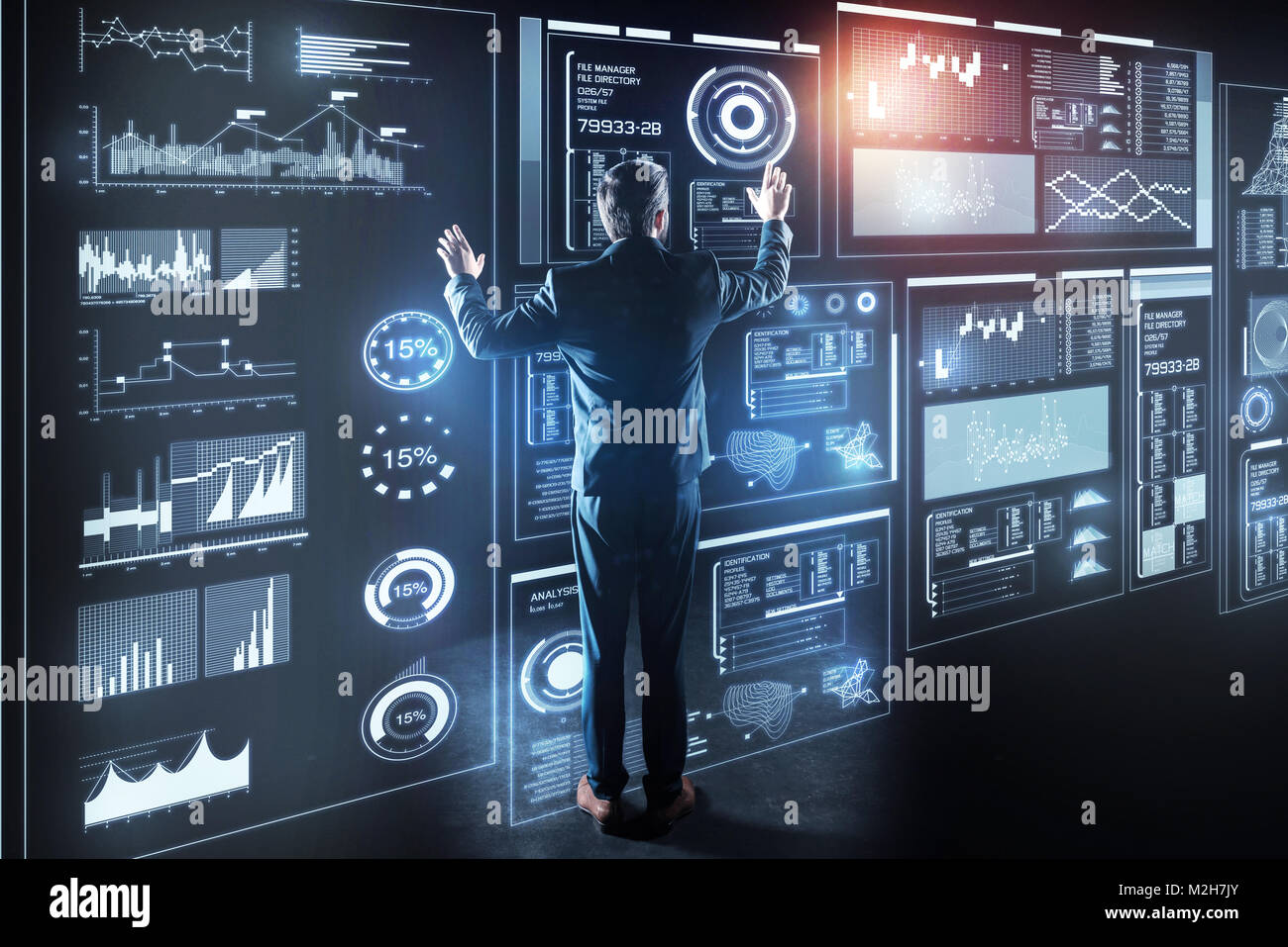 Elegant programmer standing in front of a giant transparent device and working - Stock Image