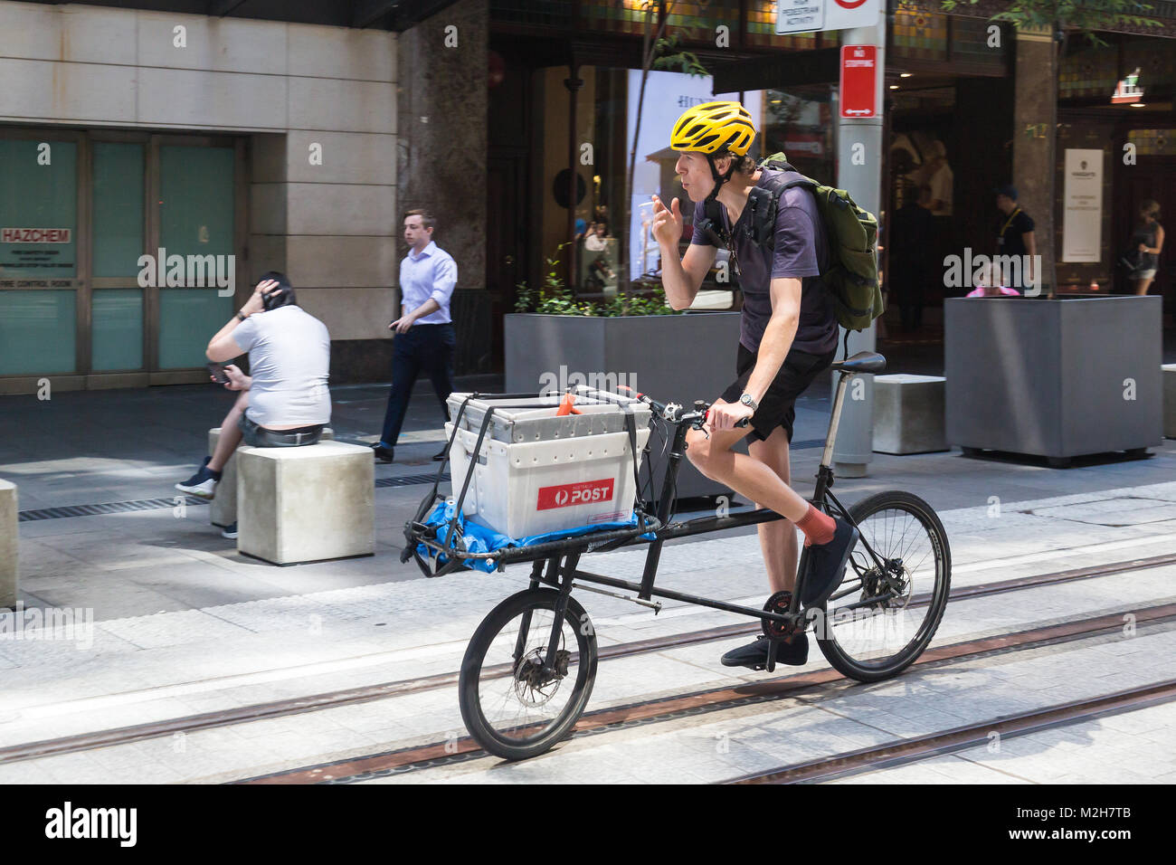 A cycle courier smokes along the new light railway construction, George Street, Sydney. - Stock Image