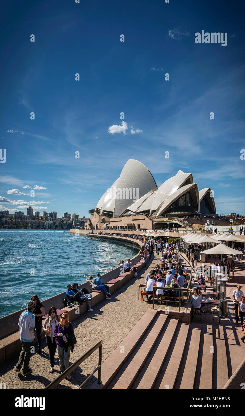sydney opera house and harbour promenade outdoor cafes in australia on sunny day - Stock Image