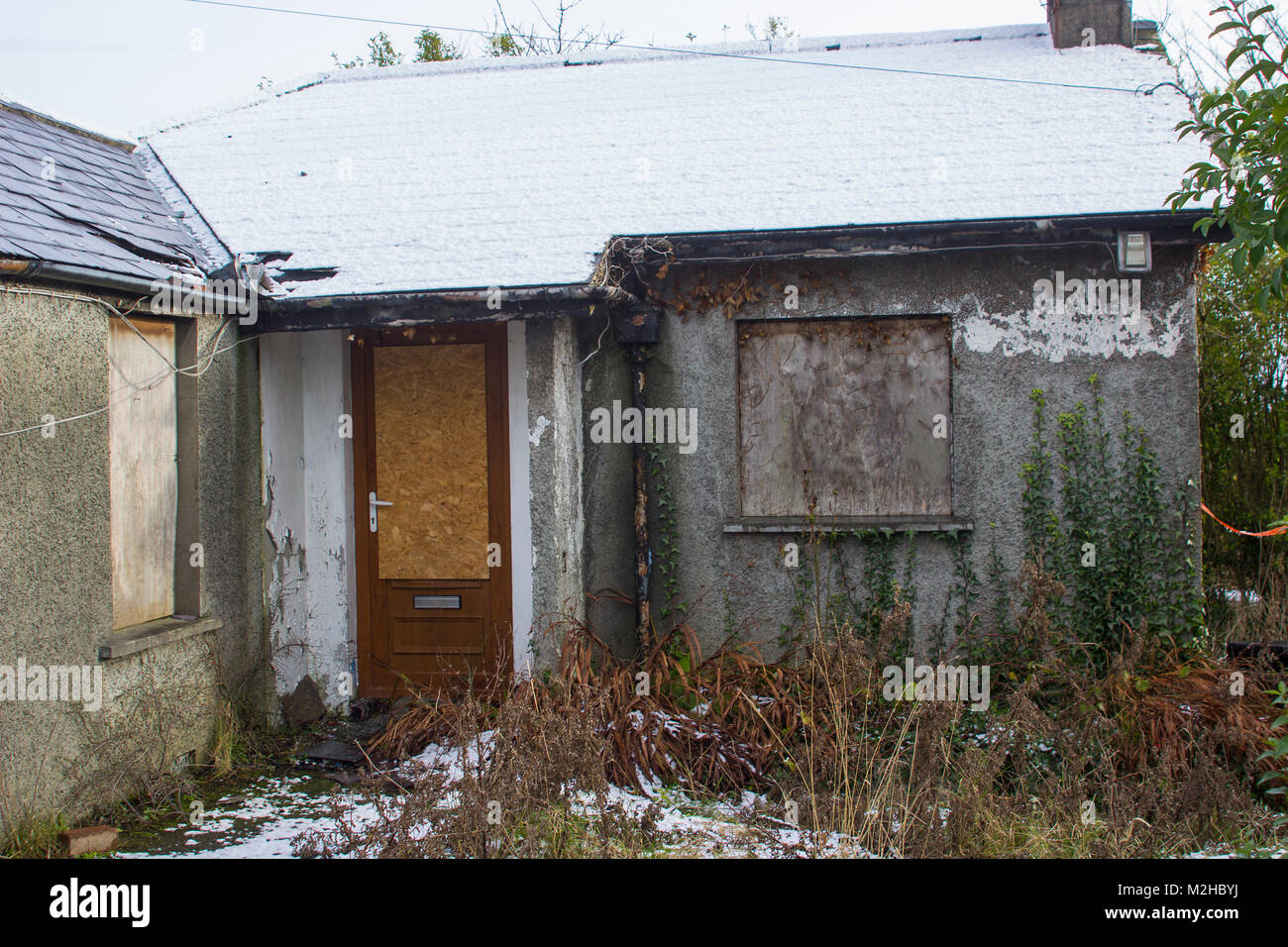 A small detached bungalow in ruins in Bangor County Down that has been unoccupied and abandoned for many years - Stock Image